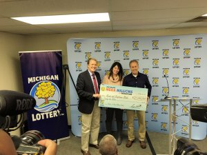 Lottery Commissioner, Aric Nesbitt, presents Mega Millions jackpot winners, Kevin and Stephanie Blake, with a check for $21 million.