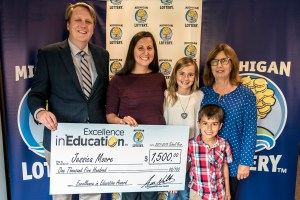 Jessica Moore poses for a photo with her daughter, Samantha Moore, mother, Nancy Chapman, son, Ethan Moore, and Michigan Lottery Commissioner, Aric Nesbitt, after accepting her Excellence in Education Award.