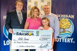 Nikki Simons poses for a photo with her husband, Terry, daughter, Lanee, and Michigan Lottery Commissioner, Aric Nesbitt, after accepting her Excellence in Education Award.