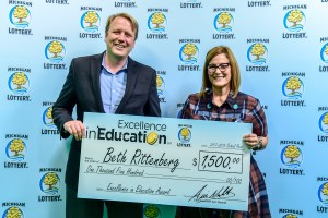 Beth Rittenberg poses for a photo with Michigan Lottery Commissioner, Aric Nesbitt, after accepting her Excellence in Education Award.