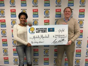 Michelle Marshall smiles after collecting her prize from Lottery Commissioner, Aric Nesbitt.