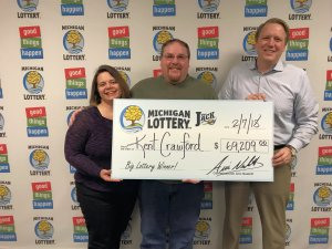 Kent Crawford (center) poses for a photo with his wife, Lynda, and Michigan Lottery Commissioner, Aric Nesbitt.