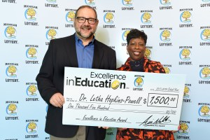 Dr. Letha Hopkins-Powell poses for a photo with Michigan Lottery Director of Public Relations, Jeff Holyfield, after accepting her Excellence in Education Award.