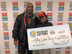 Kelley Suber-Perry and her husband, Eric, smile after collecting a $25,000 a year for life Lucky For Life prize.