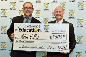 Adam Vallas (right) poses for a photo with Michigan Lottery public relations director, Jeff Holyfield, after accepting his Excellence in Education Award.