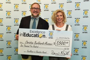 Christine Burkhardt-Messner poses for a photo with Michigan Lottery public relations director, Jeff Holyfield, after accepting her Excellence in Education Award.