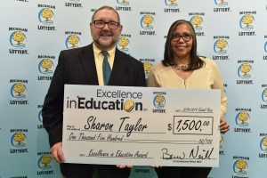Sharon Taylor (right) poses for a photo with Michigan Lottery public relations director, Jeff Holyfield, after accepting her Excellence in Education Award.