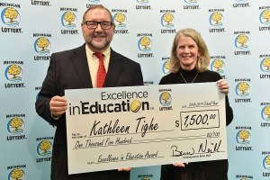 Kathleen Tighe (right) poses for a photo with Michigan Lottery public relations director, Jeff Holyfield, after accepting her Excellence in Education Award.
