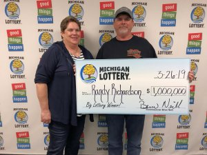 Racndy and Charlotte Richardson pose for a photo after collecting a $1 million Mega Millions prize.