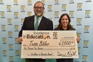 Tessa Bibler (right) poses for a photo with Michigan Lottery public relations director, Jeff Holyfield, after accepting her Excellence in Education Award.