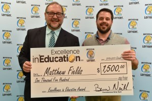 Matthew Fields (right) poses for a photo with Michigan Lottery public relations director, Jeff Holyfield, after accepting his Excellence in Education Award.