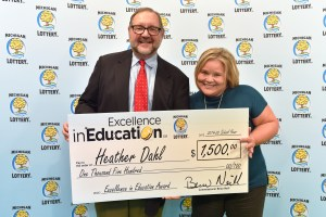 Heather Dahl (right) poses for a photo with Michigan Lottery public relations director, Jeff Holyfield, after accepting her Excellence in Education Award.