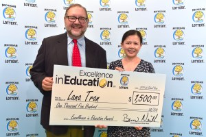 Lana Tran (right) poses for a photo with Michigan Lottery public relations director, Jeff Holyfield, after accepting her Excellence in Education Award.