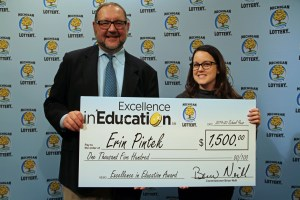 Erin Pintek (right) poses for a photo with Michigan Lottery public relations director, Jeff Holyfield, after accepting her Excellence in Education Award.