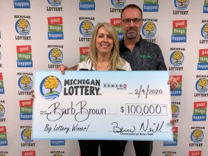 Barb Brown and her husband, Steve, pose for a photo after collecting a $100,000 Powerball prize.