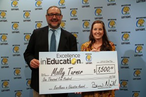 Molly Turner (right) poses for a photo with Michigan Lottery public relations director, Jeff Holyfield, after accepting her Excellence in Education Award.