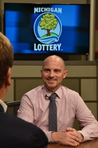 Jason Perrin is interviewed after being presented with an Excellence in Education award from the Michigan Lottery.