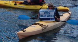 A woman floats in a kayak while holding up a sign advocating for clean water. Photo by Dylan Deprey.