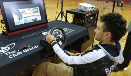 "Tenor High School student Henry Ortiz tries out the AAA distracted driver simulator during AT&T's ""It Can Wait"" event at the school."