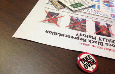 """No takeover"" buttons were worn and handed out by concerned community members. Photo by Dylan Deprey"