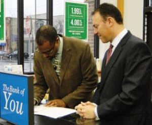 Deshea Agee, executive director for the King Drive BID and Michael Kellman, senior vice president, consumer lending at North Shore Bank sign the formal agreement launching the loan fund. Photo by Melissa Warner.