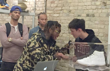 Reggie Bonds talks to a fan during his album listening party at Trusted Kicks in downtown Milwaukee. (Photo by Dylan Deprey)