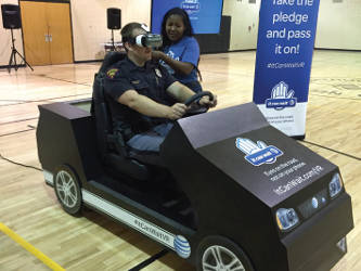 "State Trooper Michael Lawson takes a spin on the ""It Can Wait"" texting and driving simulator. Photo by Dylan Deprey"