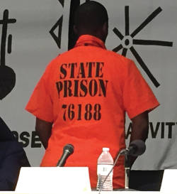 Troy Hawkins sporting an orange prison jumpsuit. He uses his experience to teach kids in the community about staying out of prison. (Photo By Dylan Deprey)