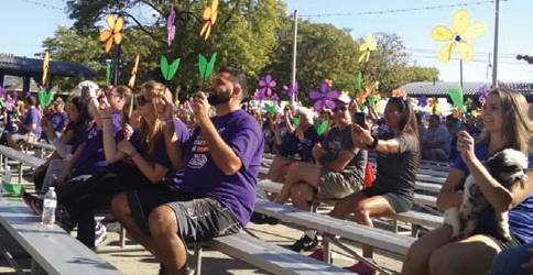 Walkers take selfies with their flowers that represent their reason for attending the walk. (Photo by Mrinal Gokhale)