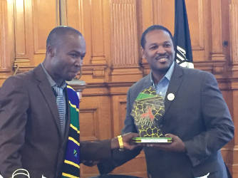 Misiwa and Hamilton holding the Tarime District's gift to Milwaukee. (Photo by Dylan Deprey)