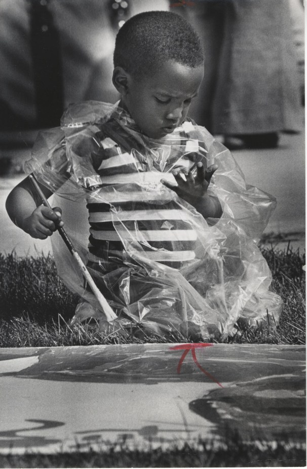 Jamin Mahan, 4, of Milwaukee found that even wrapped in plastic he could still get paint on himself. He was working on a mural. August 4, 1977.