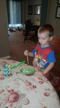 Tahoe starts his sea turtle project by painting a paper plate.