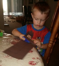 With a combination of scissor practice and tearing, Tahoe cut out pieces of brown construction paper for the project.
