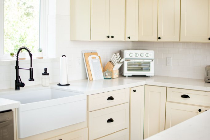 My Farmhouse Kitchen in the Mountains. Clean, bright, white kitchen but not white cabinets with pops of black. Mountain house kitchen that's light, bright, and clean. Linen colored cabinets, stainless steel appliances, matte white oven and pops of black hardware make this mountain kitchen farmhouse ready. Not too big, or too small this medium sized kitchen is the perfect size for baking and cooking. Plus it's large island has plenty of room for cooking and entertaining! Amazing farmhouse kitchen #kitchen #farmhosuekitchen #kitchendesign #cleankitchen #whitekitchen #notwhitekitchen #brightkitchen #kitchendecor #mountainkitchen #farmkitchen #modernkitchen #beautifulkitchen #blackhardware