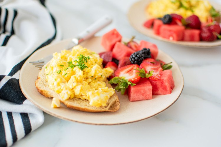 The best easy Fluffy Scrambled Eggs recipe! Use Organic Valley Eggs, butter and sour cream to make the best simple fluffy scrambled eggs. Serve these amazing scrambled eggs over toast or alone with fruit for a healthy and delicious organic breakfast! The best organic healthy breakfast recipe.