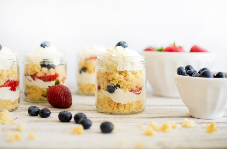 Summer Cake Jars are light, refreshing and easily adaptable! These fun little cake jars are an easy, yet impressive cake recipe. We always use organic ingredients, include a variation for gluten free baking, and also a quick switch to bake at high altitude! Check out the recipe now! #cakejars #fourthofjuly #redwhiteblue #cakejarrecipe #whippedcreamcake #freshfruit #fruitcake
