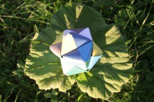 Een stervorm, veelzijdig, gevouwen van gekleurde stroken papier.