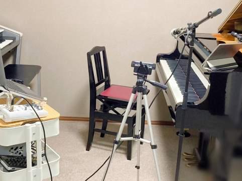 ピアノ、エレクトーン、macbook、ipad、マイク、マイクスタンド、オーディオ機器、ケーブル、カメラ、三脚、黒い椅子、銀色、ジュータン、壁