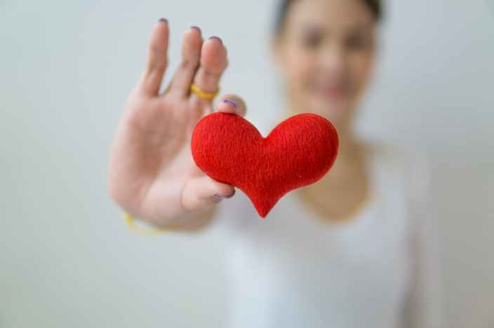 anonymous woman showing small heart