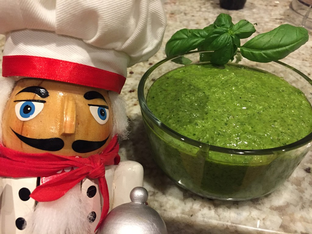 bright green homemade basil pesto in a clear glass bowl with a sprig of fresh basil on the rim of the bowl. There's a nutcracker in the foreground who looks like a chef.