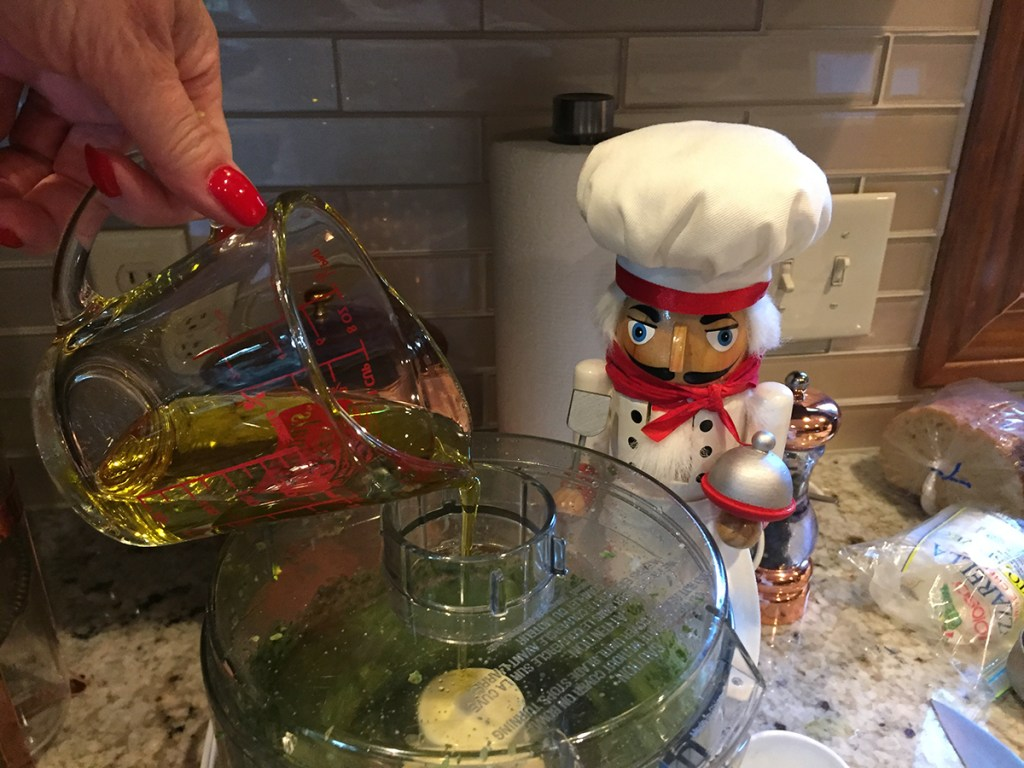 Adding the oil to the food processor to make fresh basil pesto. There's a nutcracker in the foreground who looks like a chef.