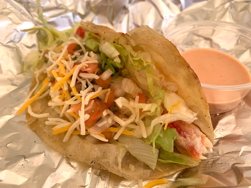 King crab taco with lettuce, cheese and pico de gallo on a four tortilla with cup of sauce, all on foil