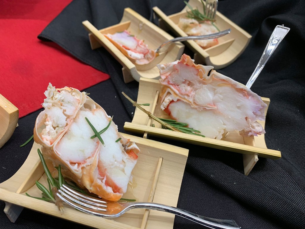 King Crab Appetizer in bamboo boats on black napkins