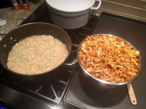 skillet with sautéed shallots, bowl with chopped chanterelles on a stove top.
