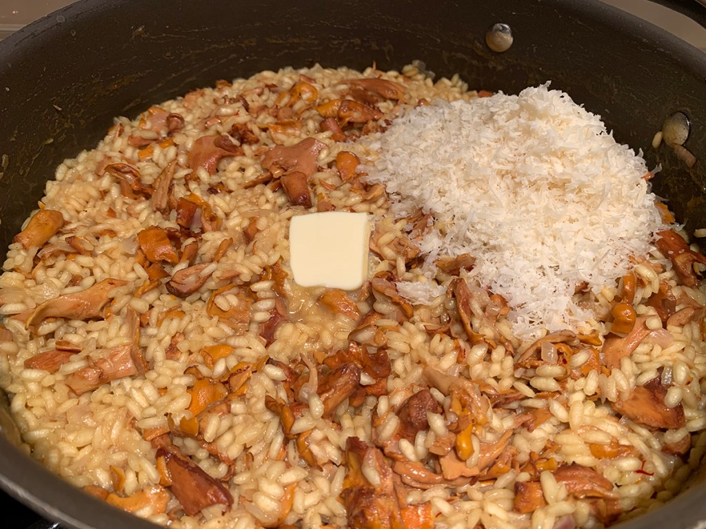 chanterelle and saffron risotto with a tablespoon of butter and cup of parmesan cheese on top, in a nonstick skillet.