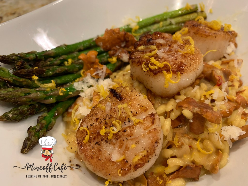 Seared scallops on a bed of a chanterelle and saffron risotto, sautéed asparagus in a white bowl by mincoff cafe
