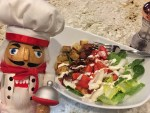 Pepe the nutcracker with a white bowl to the right of him containing a chopped salad consisting of bacon, lettuce, tomato, onion, croutons and ranch dressing