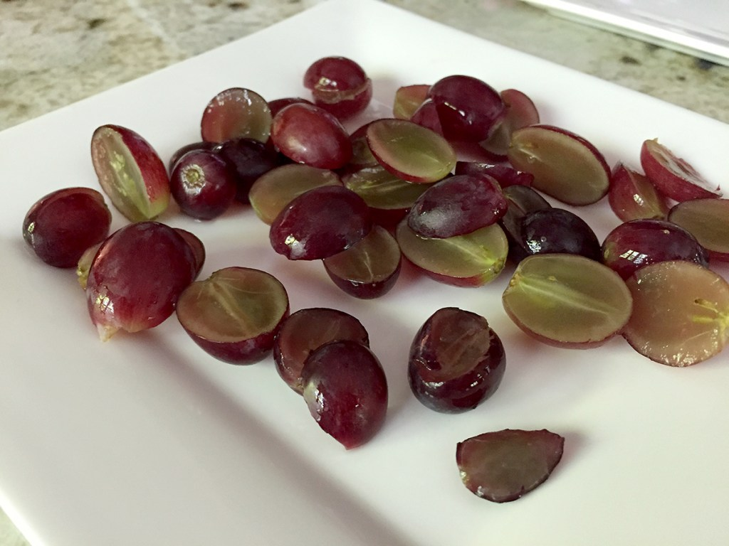 Several red grapes cut into half on a square white plate