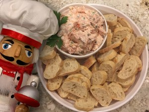 Smoked salmon dip in a white bowl, garnished with fresh parsley and inside another white bowl that has many sliced of french bread to spread it on. Pepé, the nutcracker who looks like a chef is in the foreground to the left.