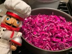 Fried red cabbage in a skillet with a nutcracker that looks like a chef in the foreground.